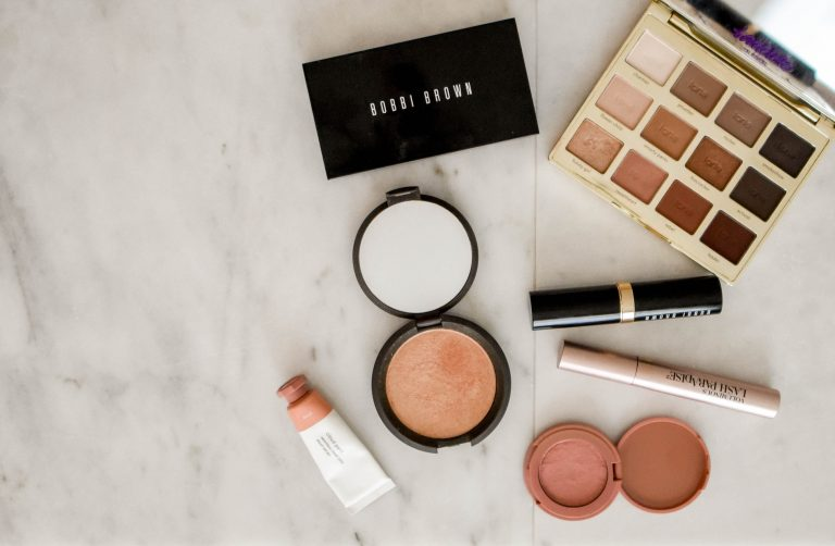photo of assorted makeup products on gray surface